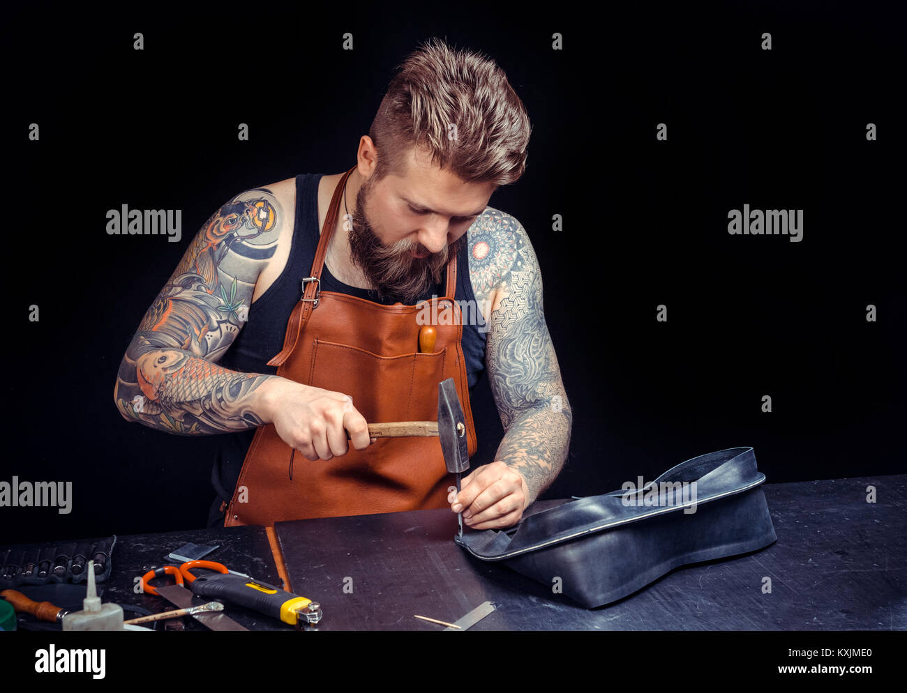 Leather Craftsman creates a new leatherwork at his shop - Stock Image