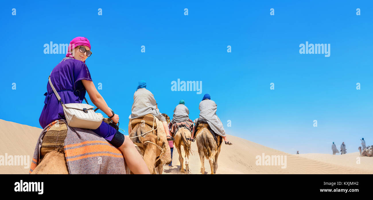 Group of tourists riding on camels. Safari tourism. Sahara desert, Tunisia, North Africa - Stock Image