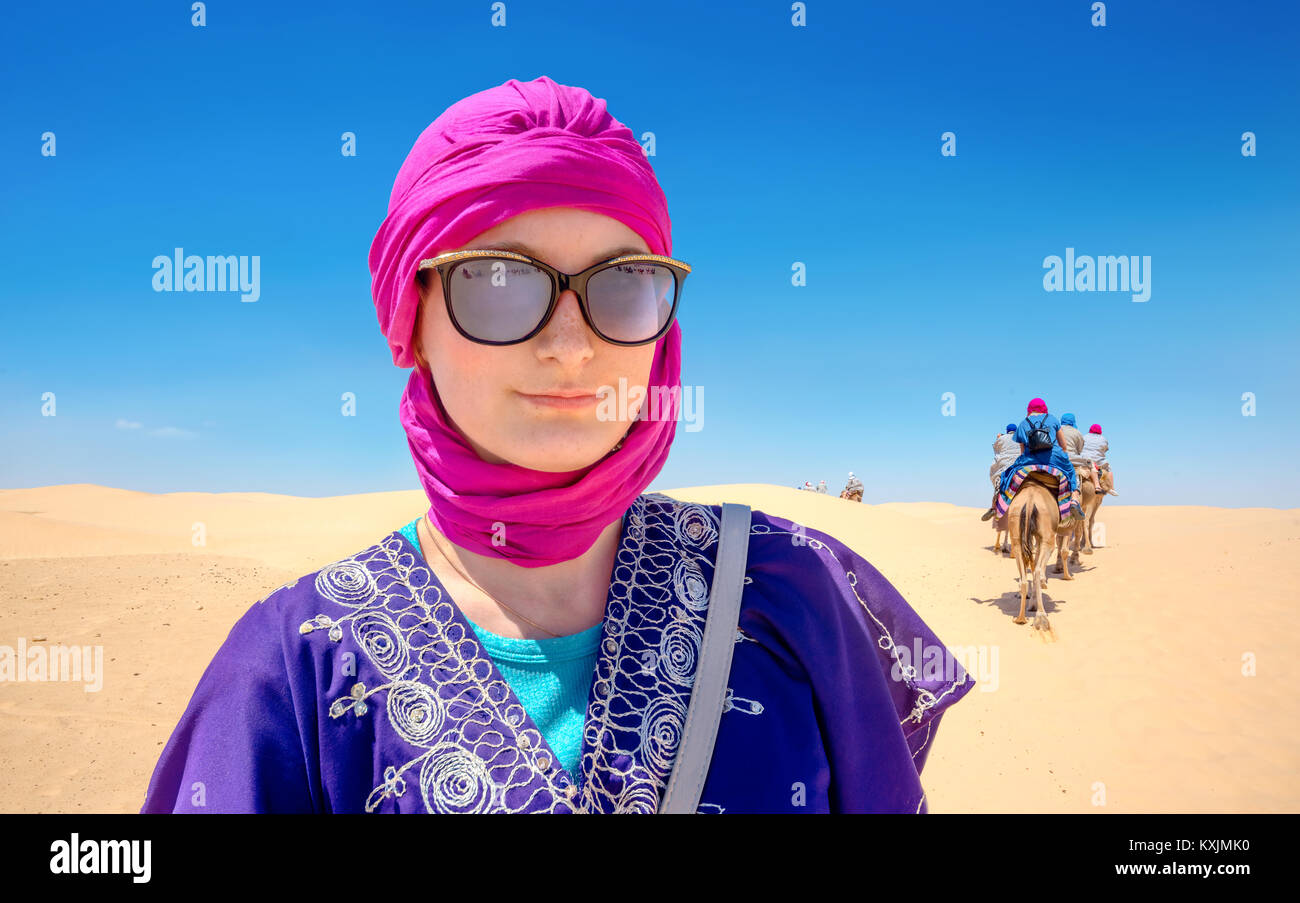Portrait of beautiful woman in arabic traditional clothing against background of tourists riding on camels. Sahara - Stock Image