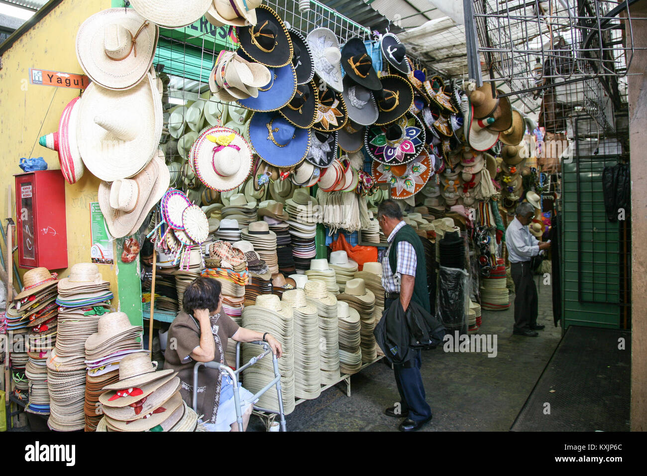 OAXACA, MEXICO - MARCH 7th, 2012: Woman selling large variety of mexican traditional hats and sombreros on a local Stock Photo
