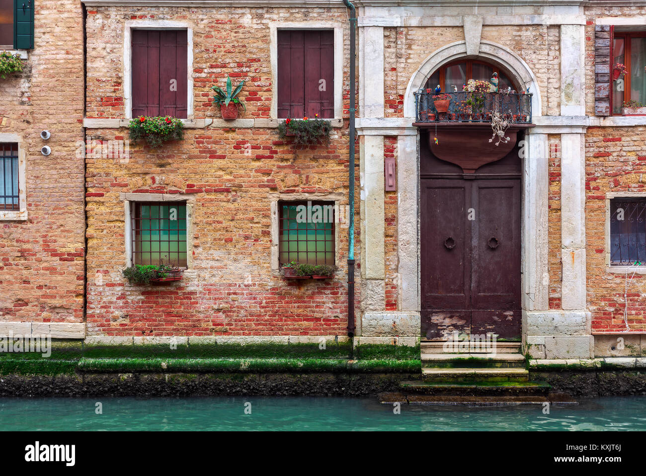 Facade of partially mossy old brick house with wooden vintage door on narrow canal in Venice, Italy. - Stock Image