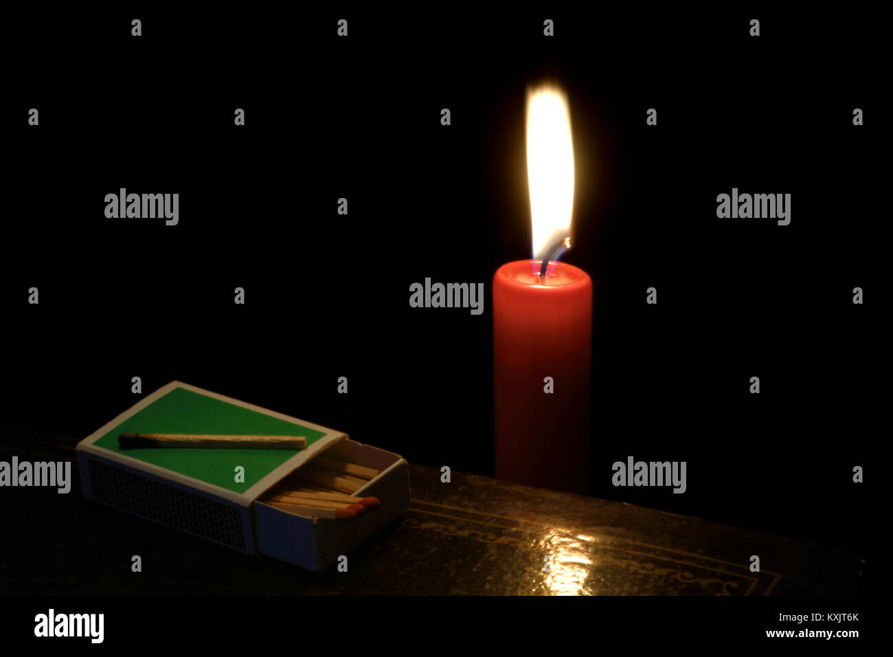 Closeup of a matchbox with a used match in the darkness on a book, with candle in the background. - Stock Image