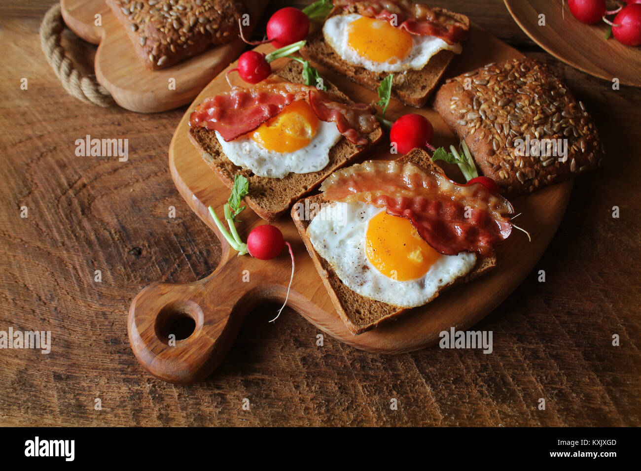 Breakfast of crispy bacon, fried eggs and bread. Sandwiches on cutting board. Rustic table - Stock Image