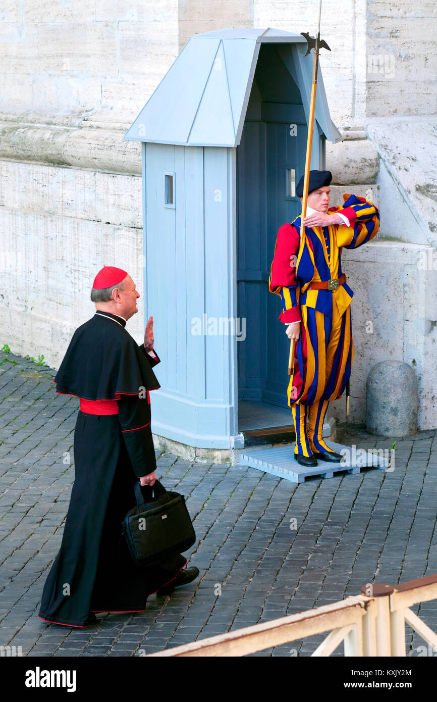 Cardinal or cleric passing Swiss Guard standing at attention, Entrance to Vatican City, Rome, Italy - Stock Image