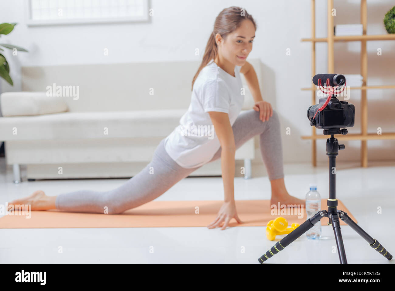 Confident trainer doing exercises and recording them for her blog - Stock Image