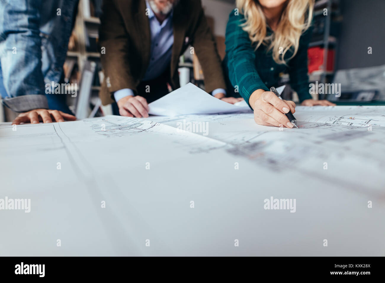 Creative business people working together on real estate projects. Close up of female hand pointing at building - Stock Image