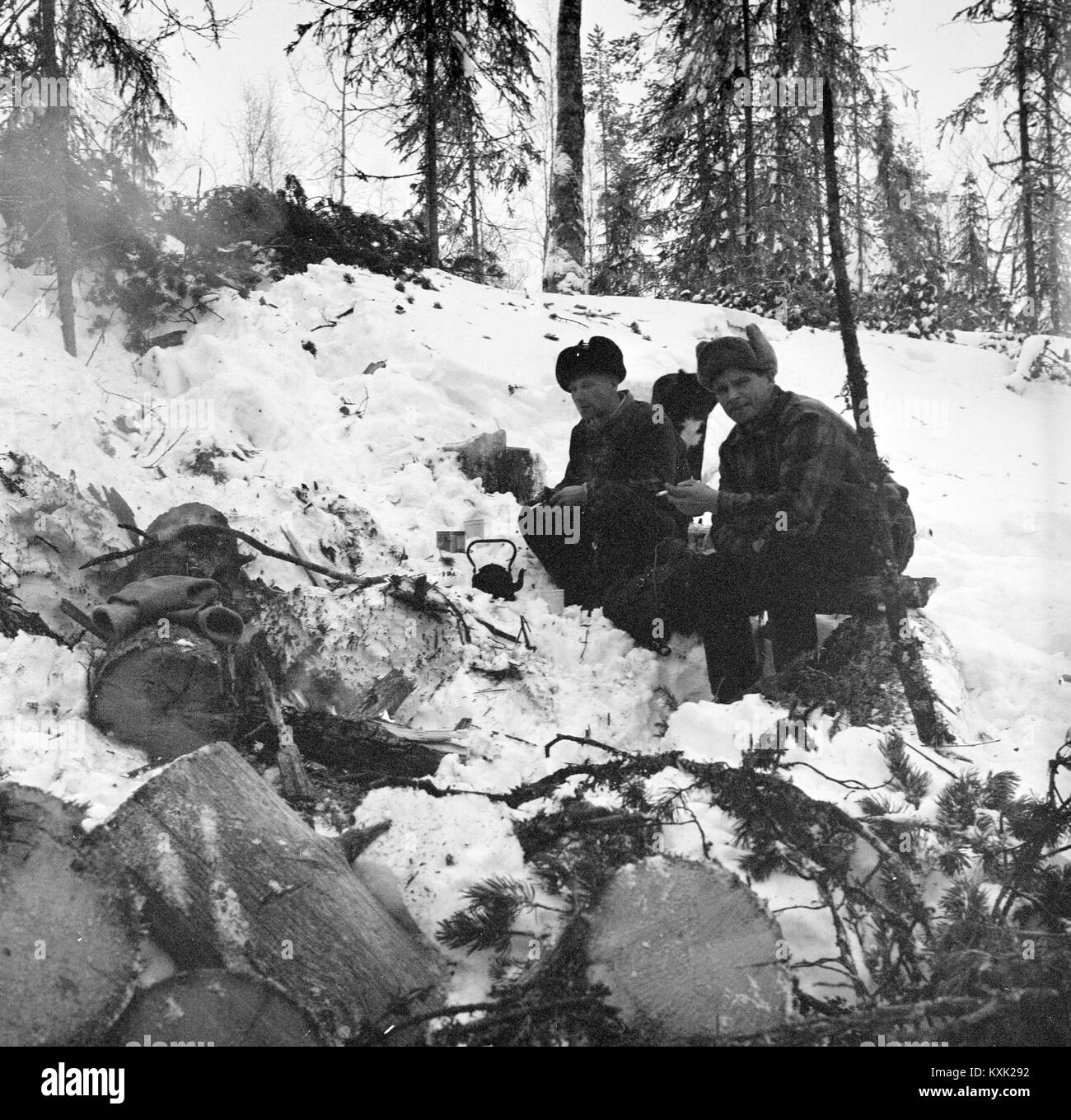 Forestry Workers Sitting By Fire Making A Hot Drink In Snow Covered Forest Finland 1959