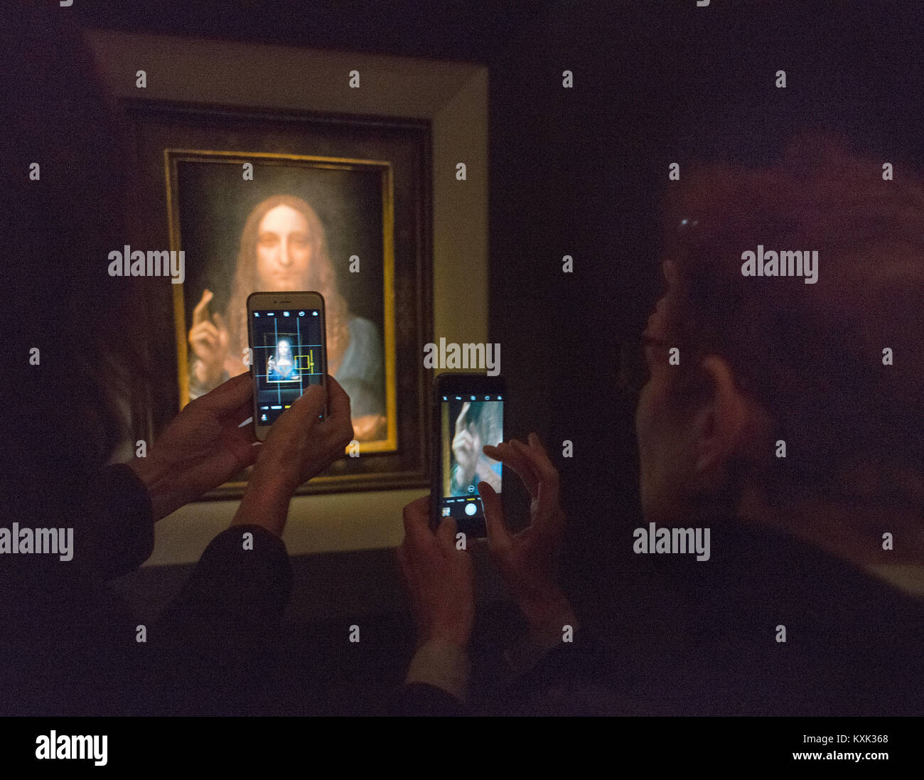 People taking picture of the Leonardo di Vinci Salvator Mundi on display at Christie's in New York City. - Stock Image