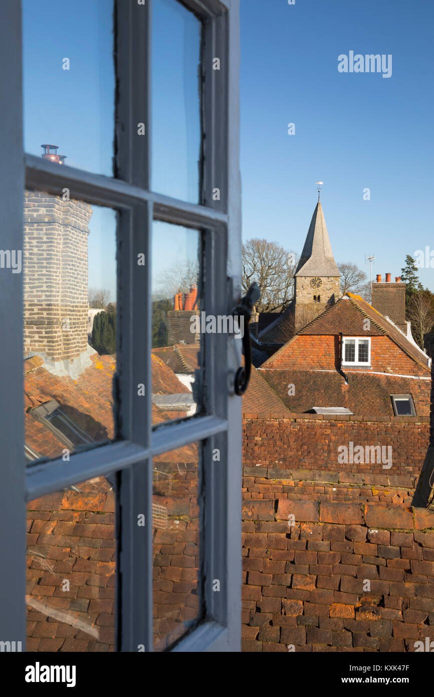 View through open window over cottage roof tops to St. Bartholomew's church, Burwash, East Sussex, England, - Stock Image