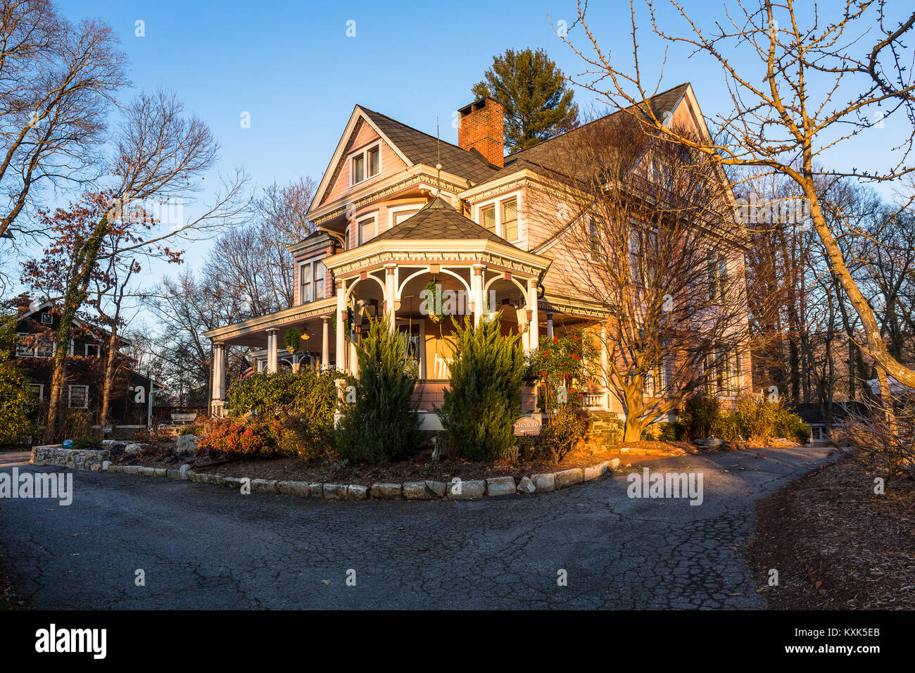 Late afternoon winter sunlight bathes an elegant Queen Anne Victorian property in Asheville, NC. - Stock Image