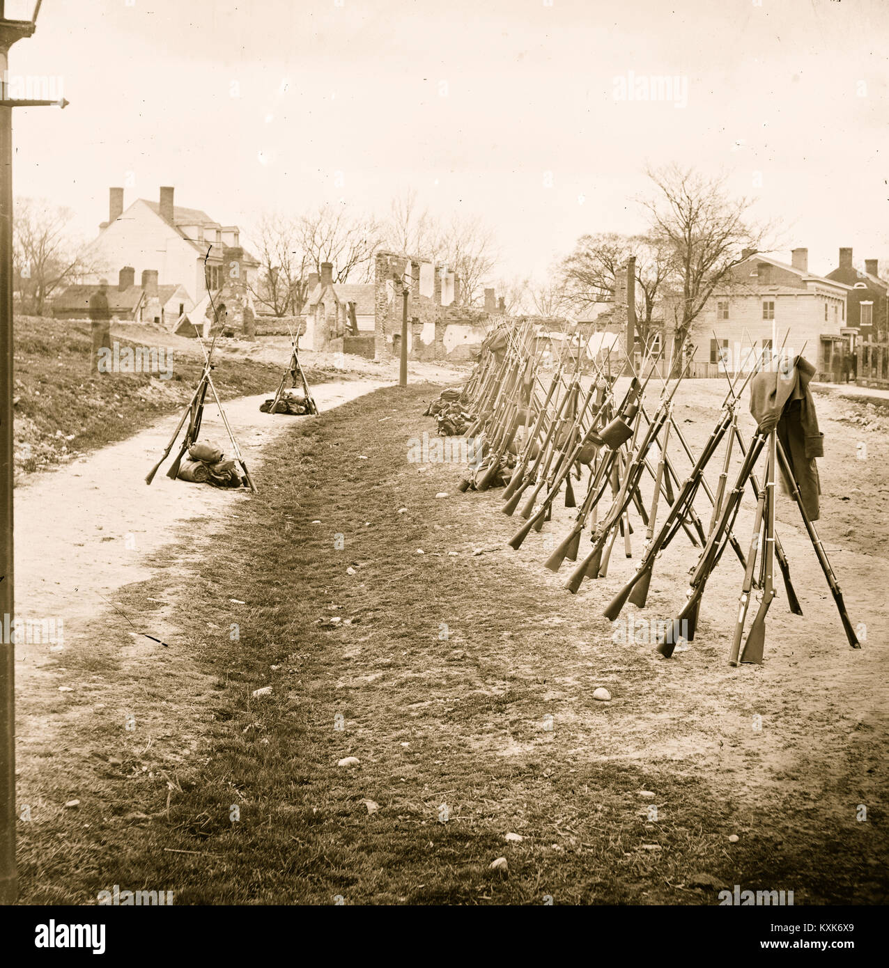 Petersburg, Va. Row of stacked Federal rifles; houses beyond - Stock Image