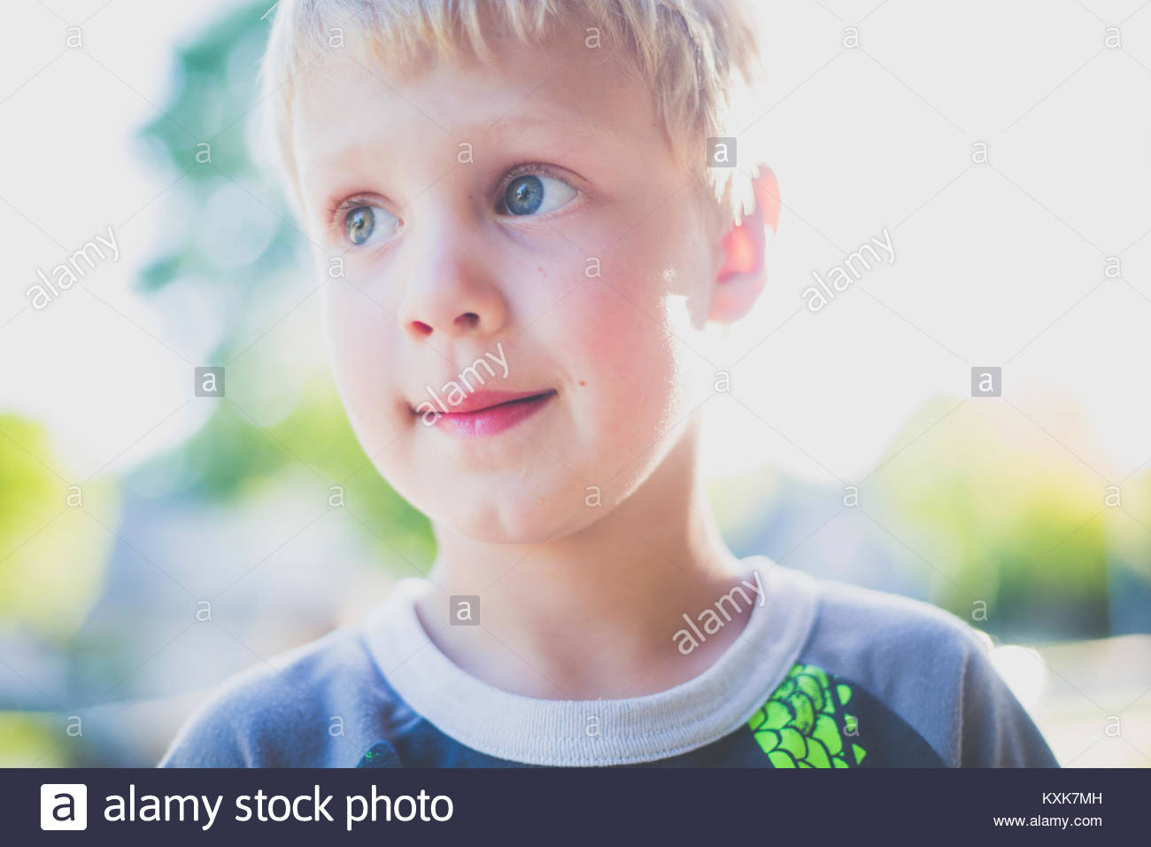 Close-up of cute thoughtful boy looking away - Stock Image