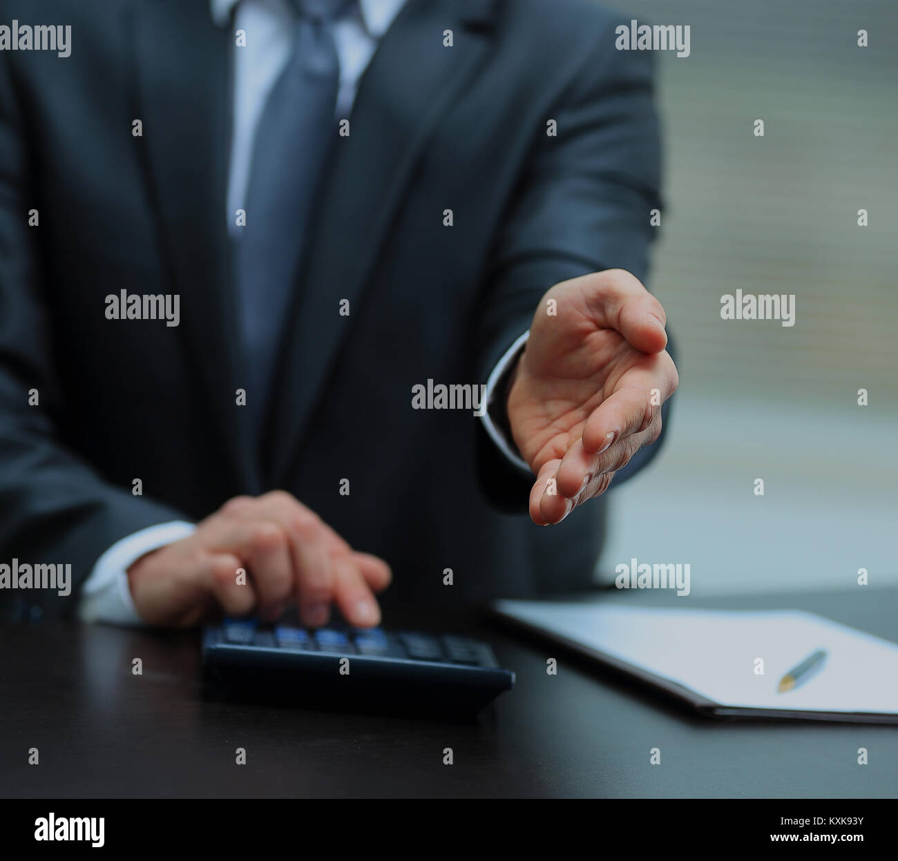 A business man with an open hand ready to seal a deal. - Stock Image