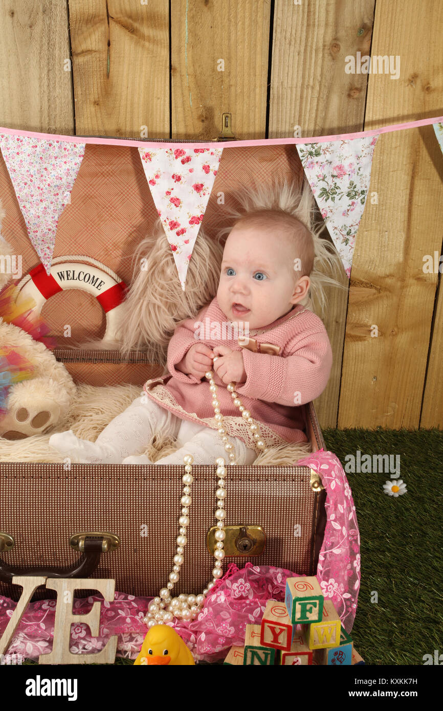 pretty baby girl sitting in suitcase playing with toys in the garden
