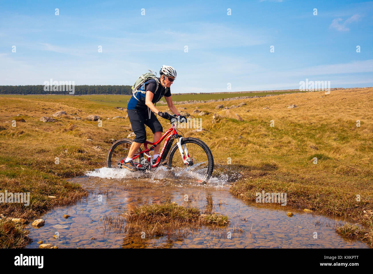 Female mountain biker splashing through a ford on Crosby Ravensworth Fell in the Yorkshire Dales National Park - Stock Image