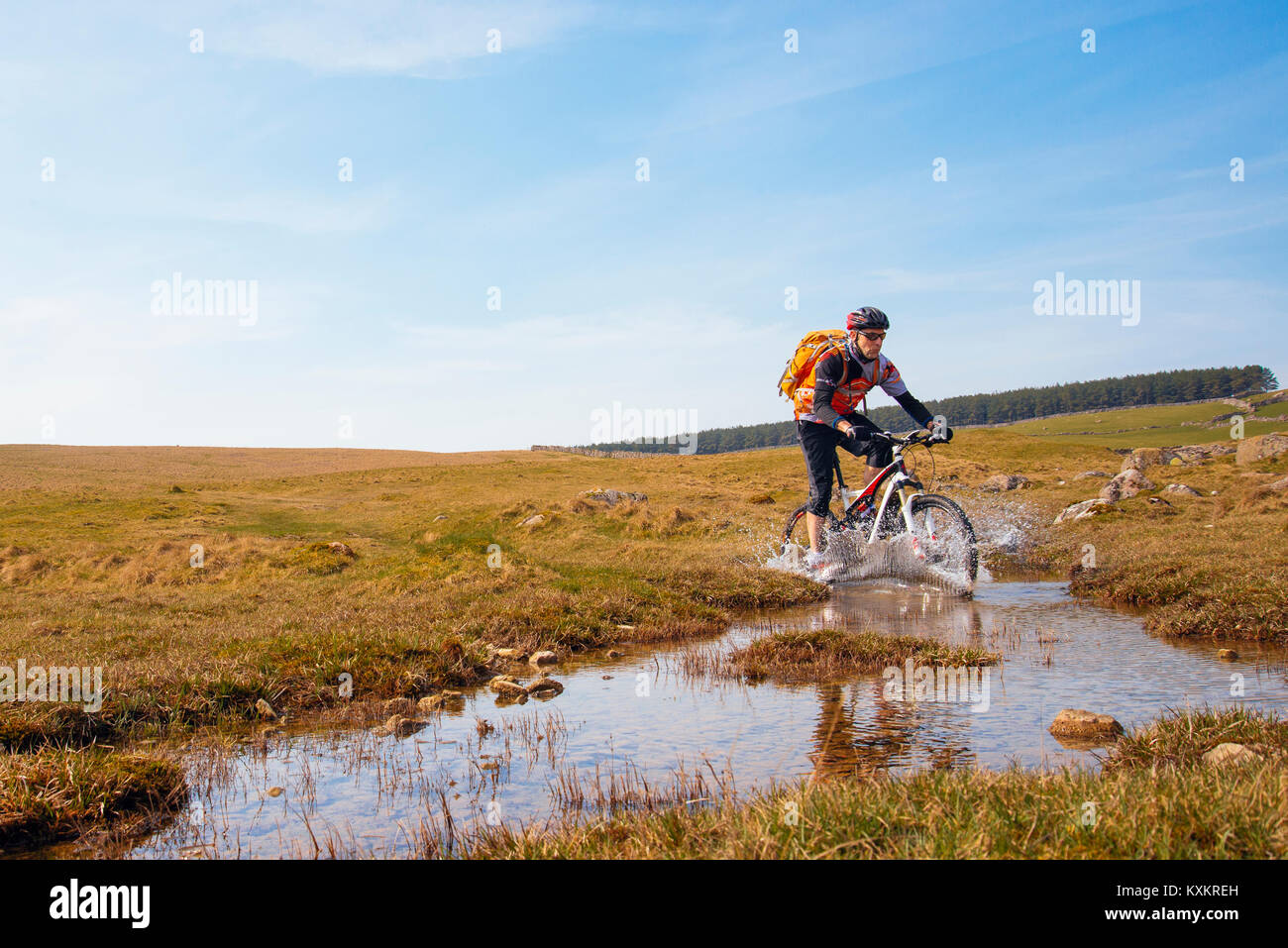 Mountain biker splashing through a ford on Crosby Ravensworth Fell in the Yorkshire Dales National Park - Stock Image