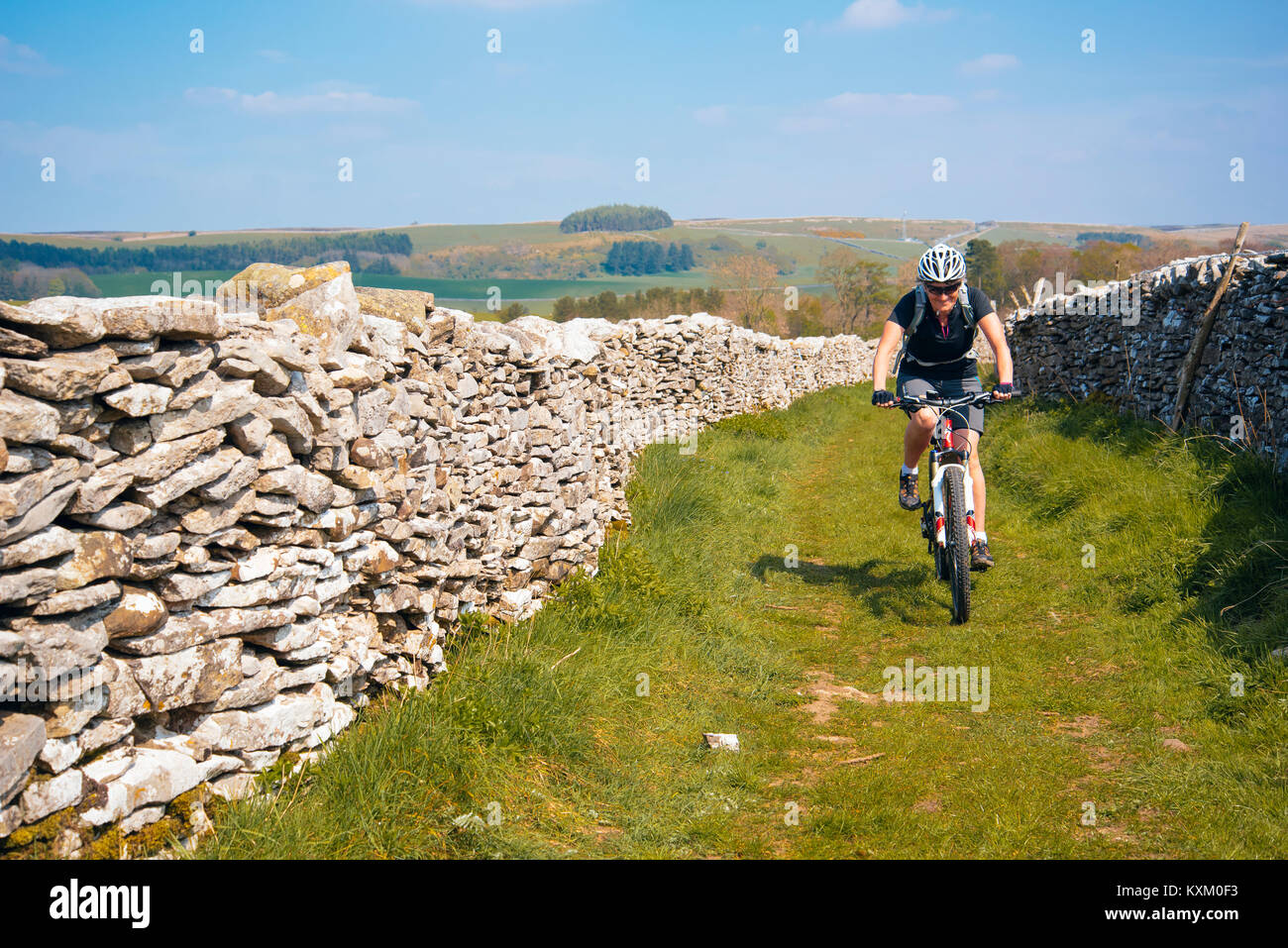 Female mountain biker on easy trail near Newbiggin-on-Lune, Cumbria - Stock Image