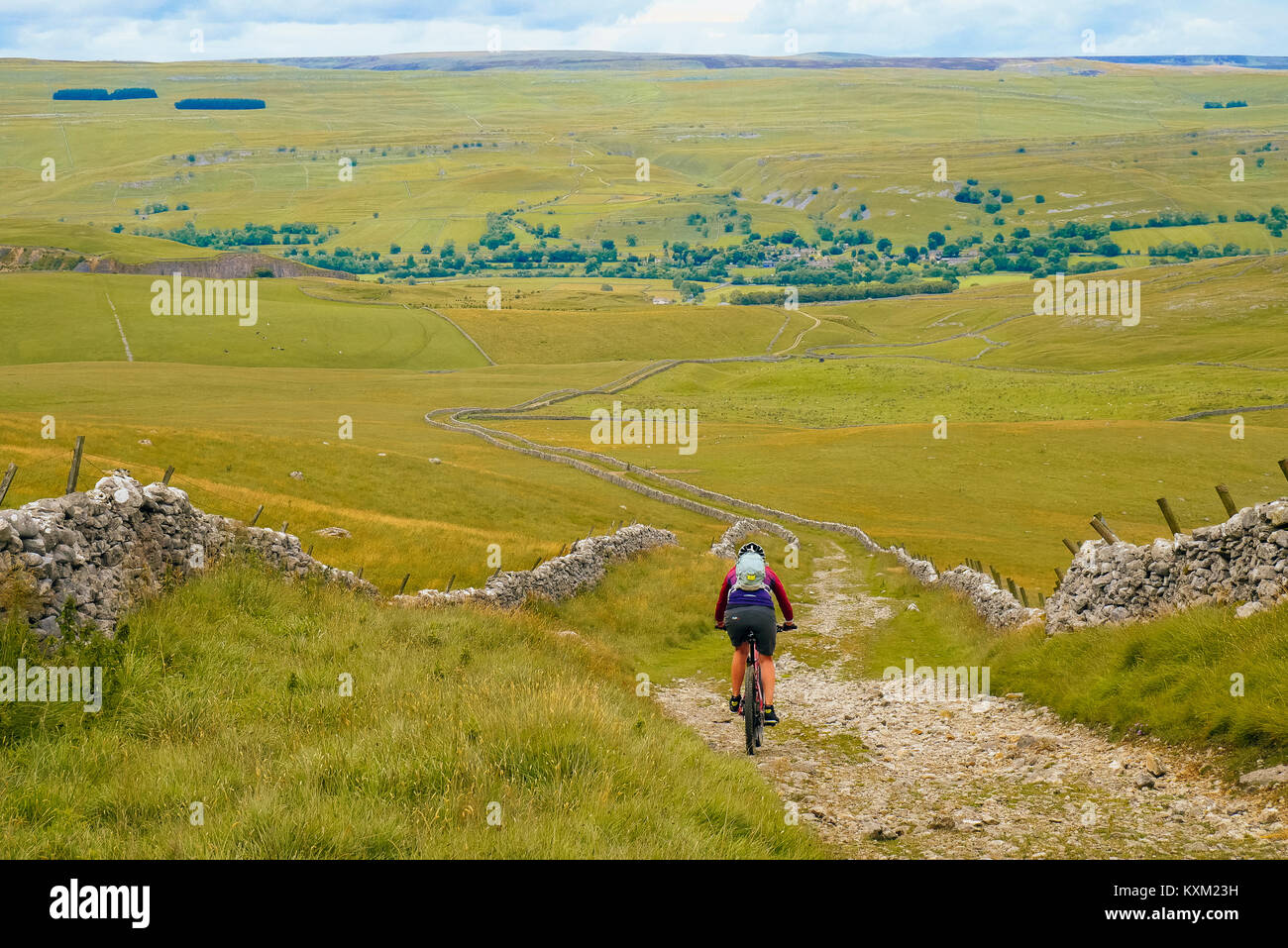 Female mountain biker on the well-known Mastiles Lane in the Yorkshire Dales, descending towards Wharfedale - Stock Image