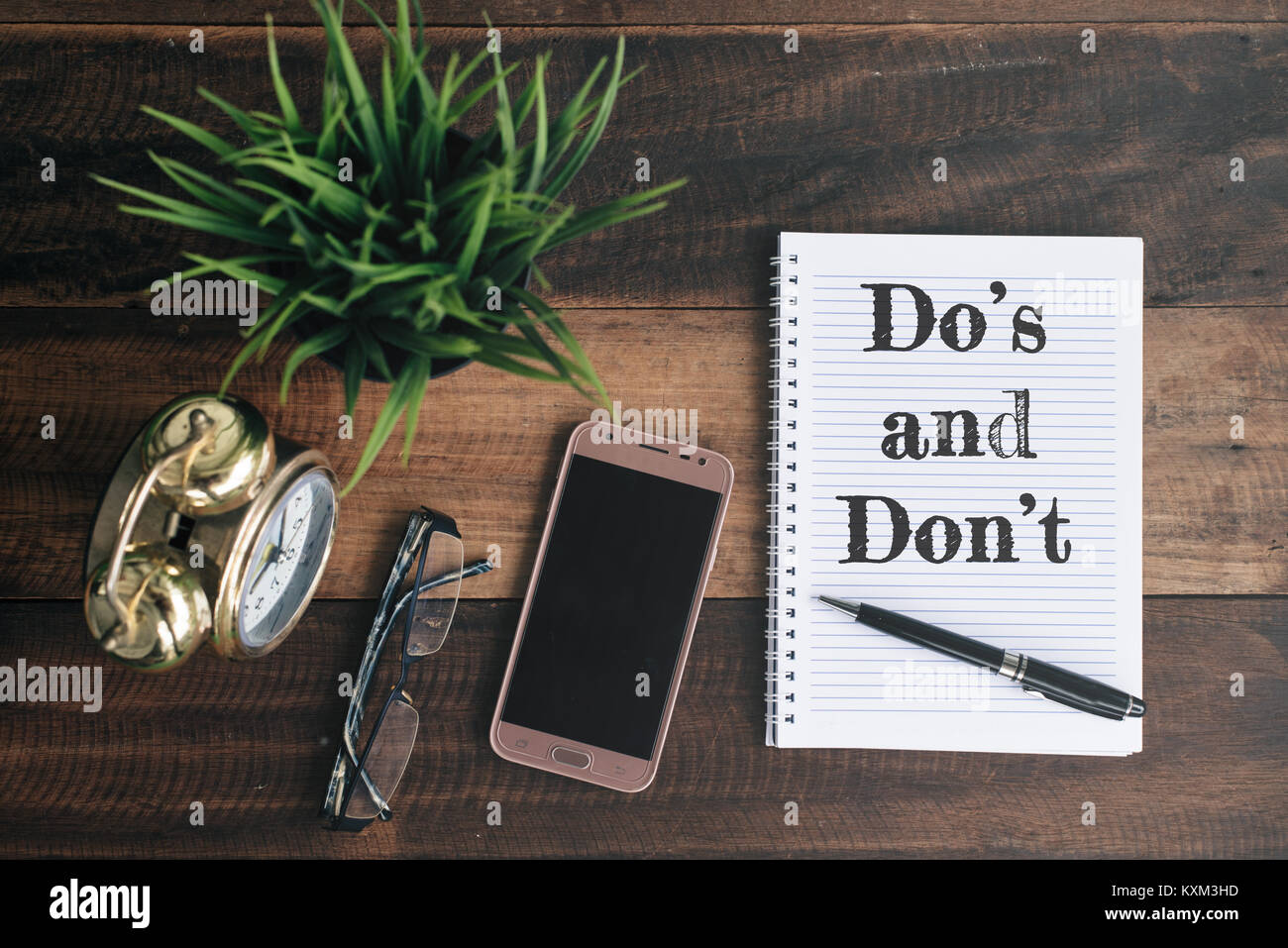 phone, glasses, clock, green plant and notebook with Do's and don't word. lifestyle concept - Stock Image