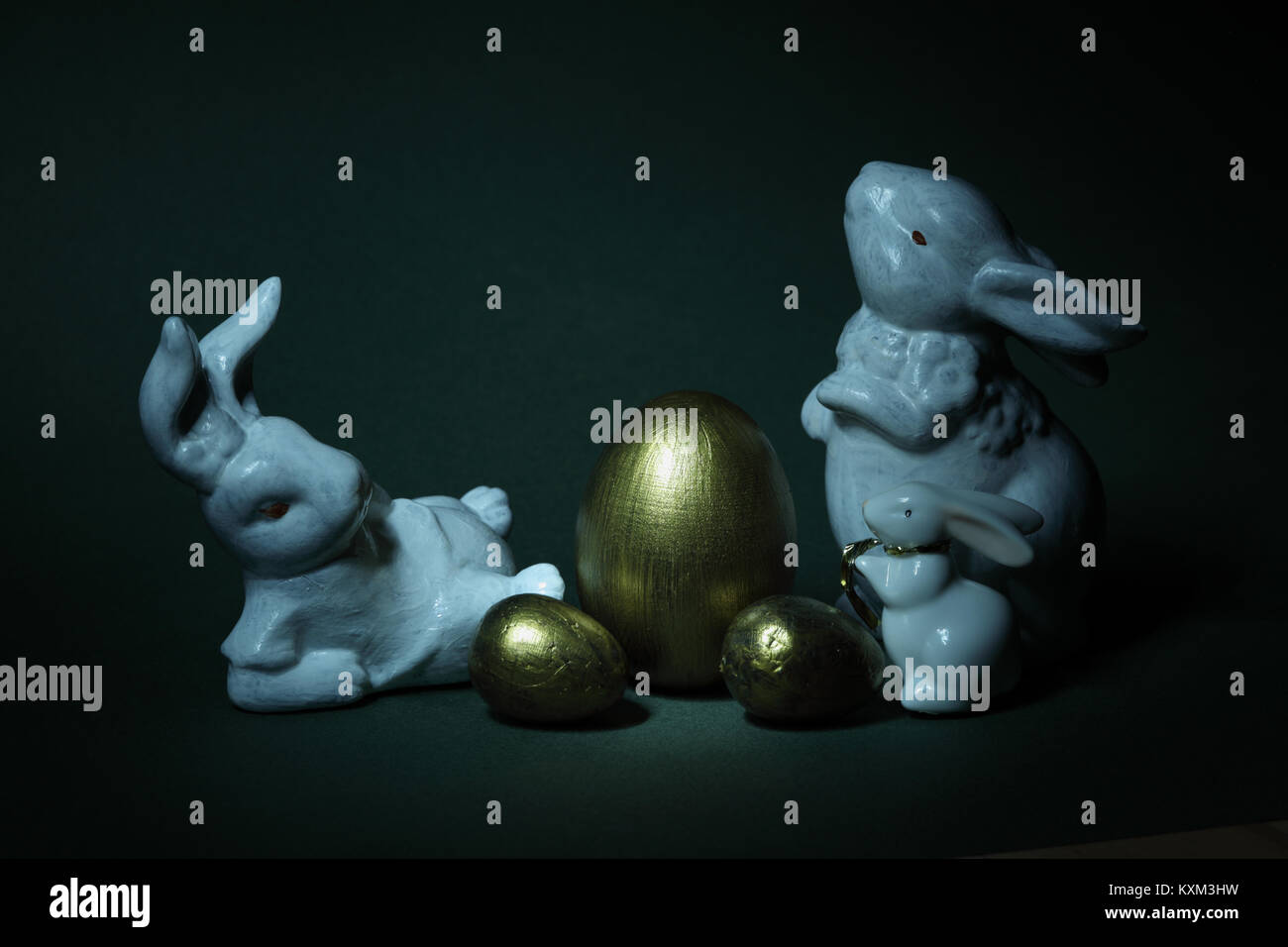 golden eggs and Family rabbits Creatively lit, against a black background - Stock Image