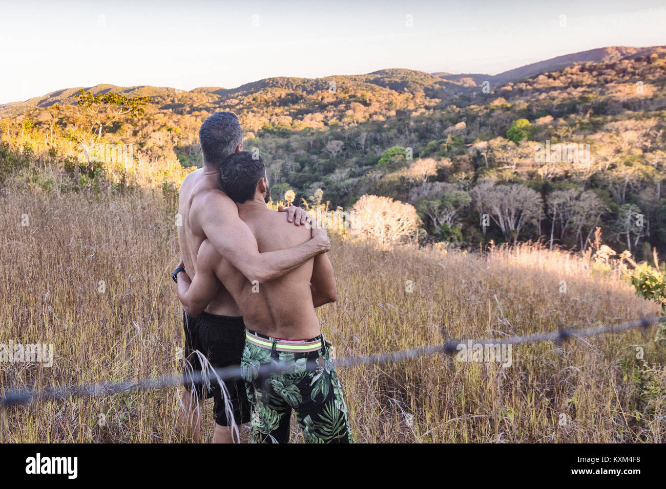 Rear view of two bare chested men looking out at landscape,Guaramiranga,Ceara,Brazil - Stock Image
