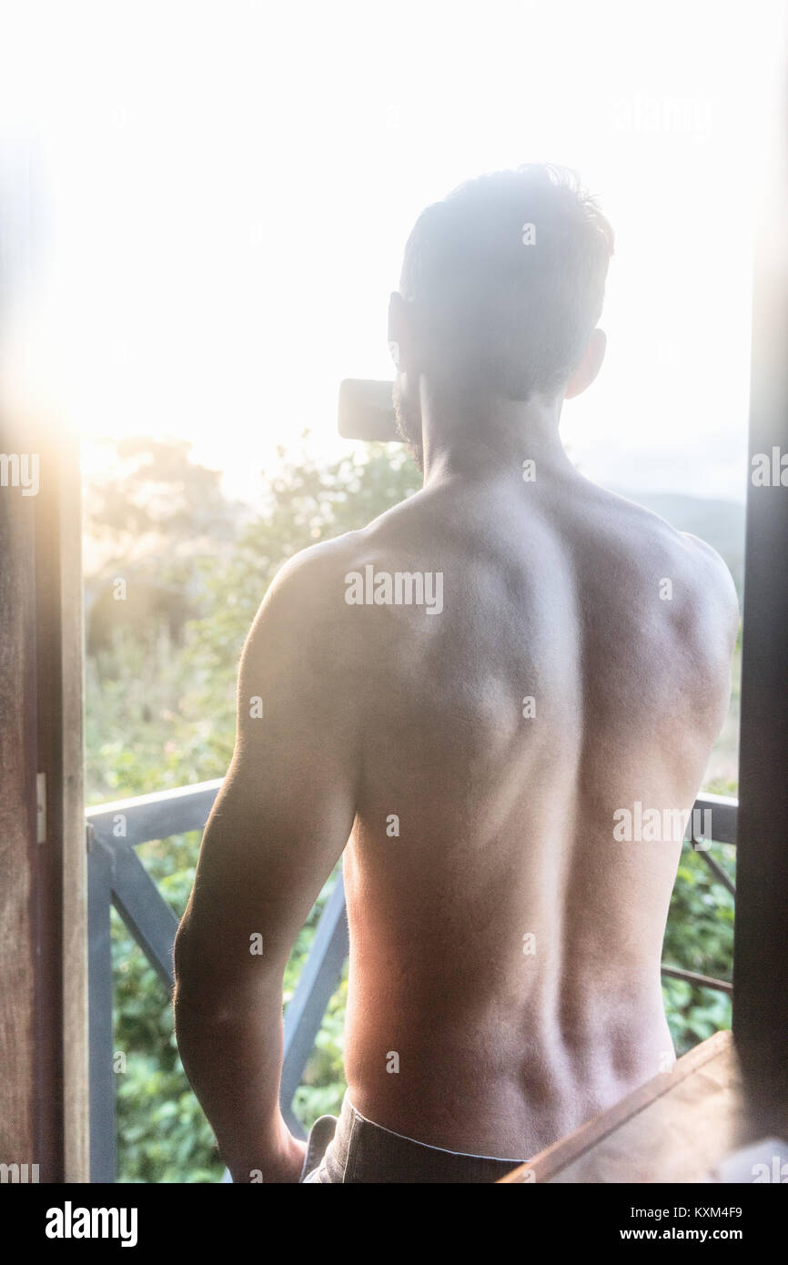Rear view of bare chested man photographing sunlit view from balcony,Guaramiranga,Ceara,Brazil - Stock Image