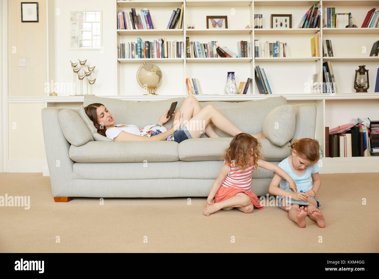 Pregnant woman reclining on sofa with smartphone and daughters sitting on floor drawing - Stock Image