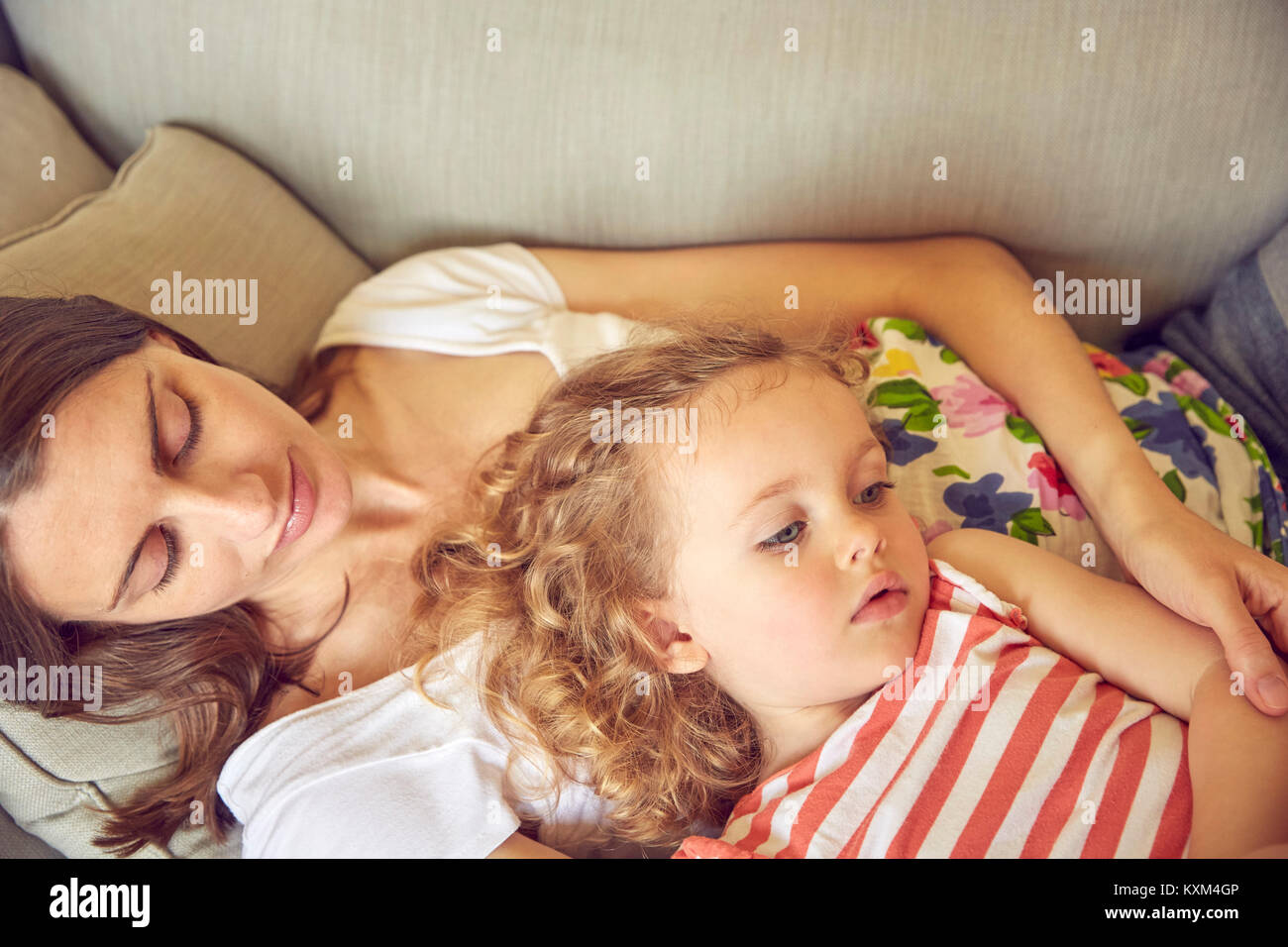 Pregnant woman and daughter reclining on sofa - Stock Image