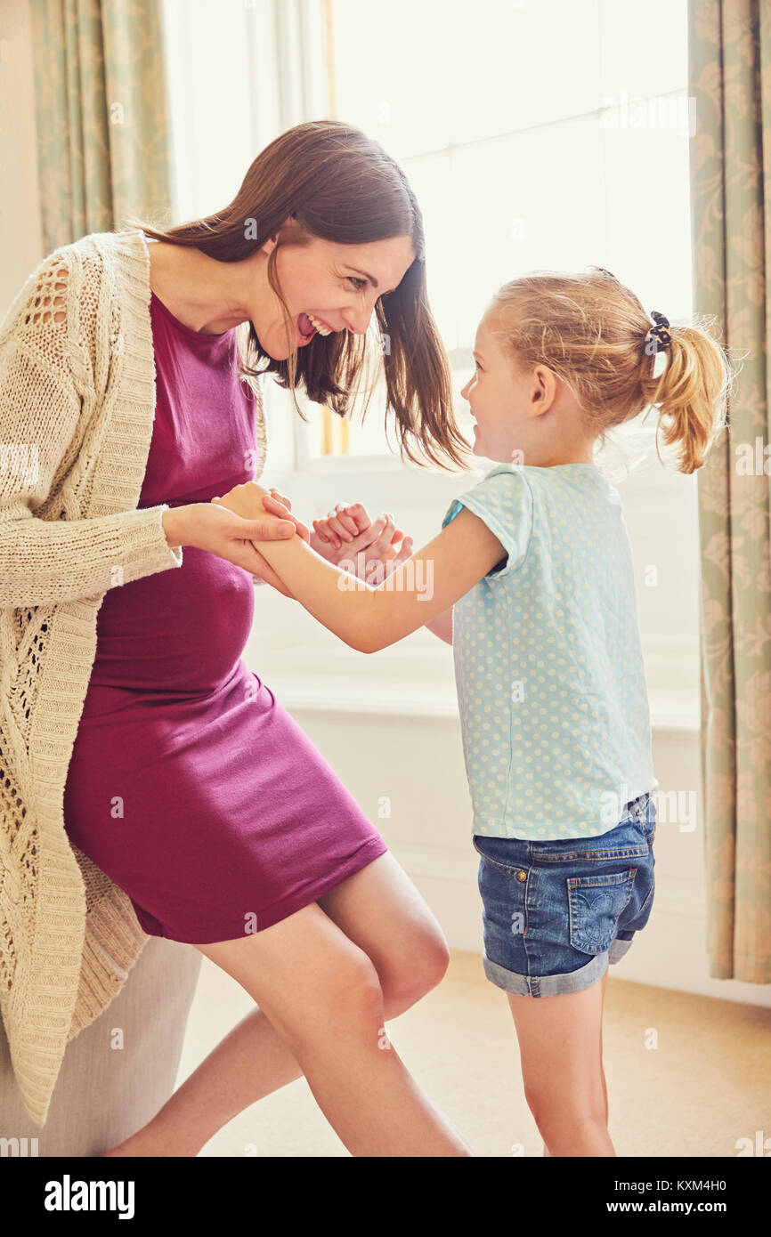 Laughing pregnant woman playing with daughter in living room - Stock Image
