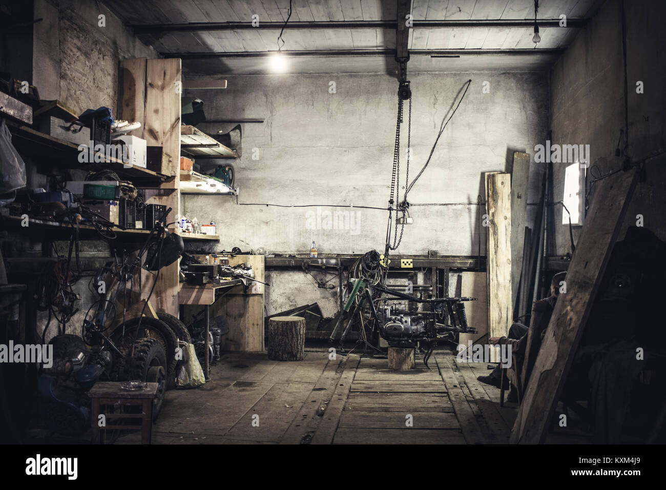 Mechanic sitting in armchair looking at dismantled vintage motorcycle in workshop - Stock Image
