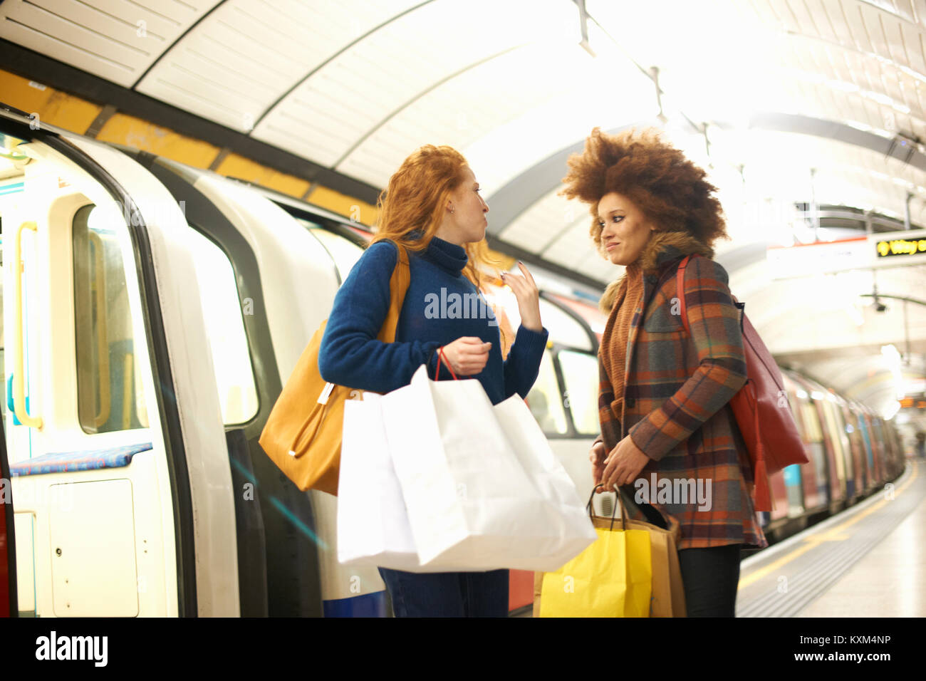 Two young women standing on underground train platform,holding shopping bags - Stock Image