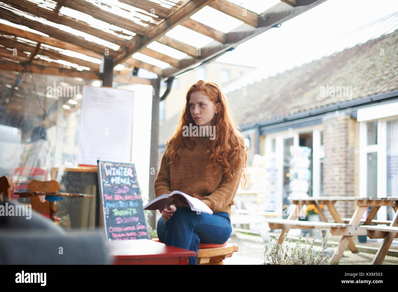 Woman at coffee shop holding notebook looking solemn - Stock Image