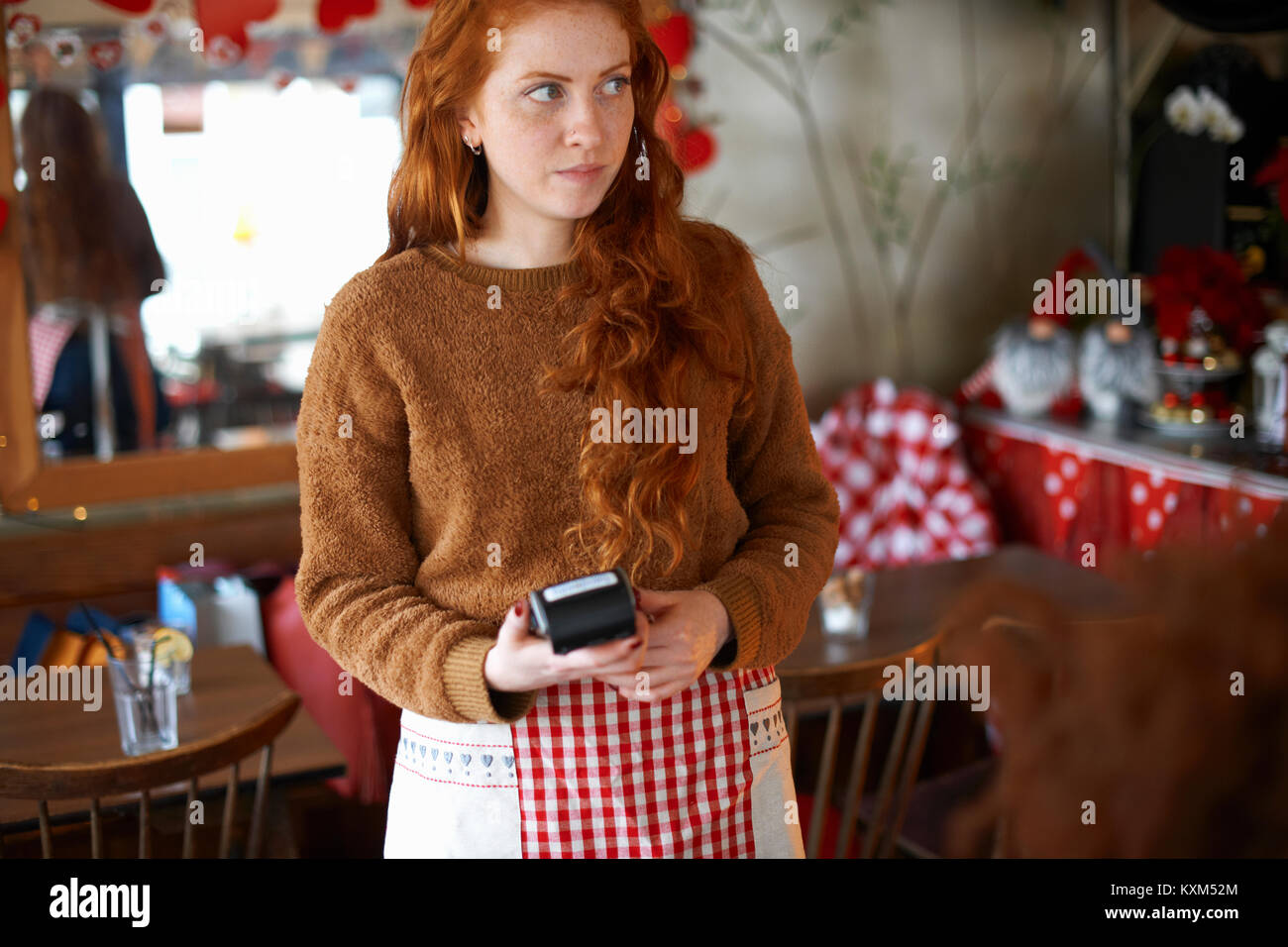 Waitress in cafe holding credit card reader Stock Photo