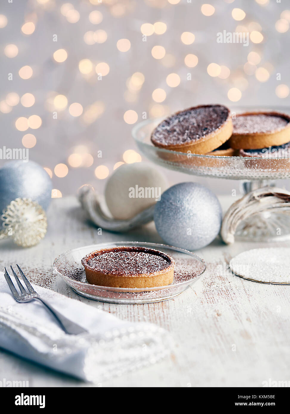 Christmas tarts dusted with sugar,Christmas baubles beside them - Stock Image