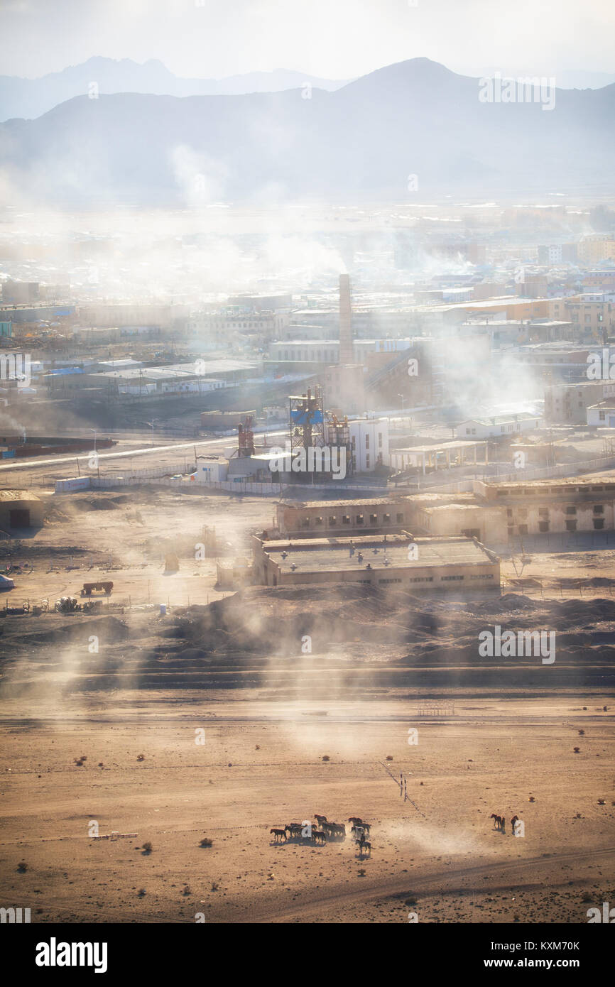 Khovd Hovd town city sunset smoke chimneys burning coal to stay warm and in cold Mongolian winter - Stock Image
