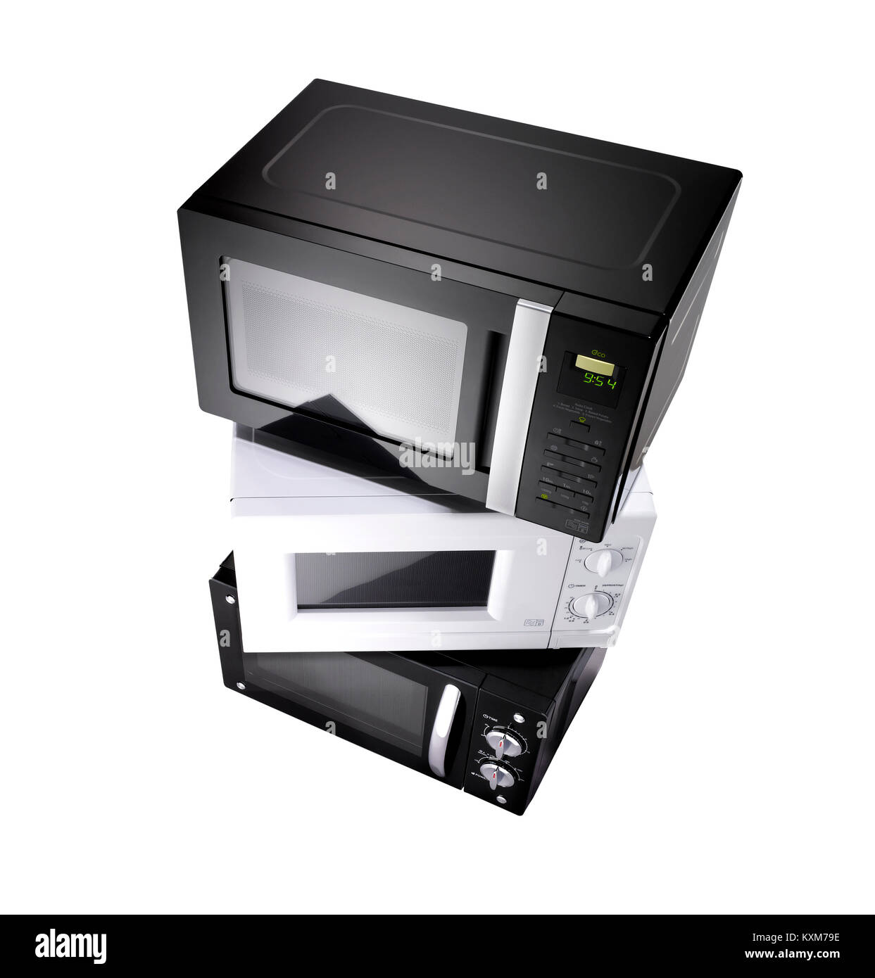 A stack of three microwaves shot with a wide angle lens on a white background - Stock Image