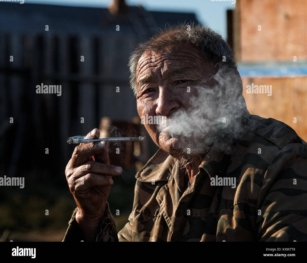 Old man smoking long cigarette portrait morning sun Mongolia ger camp Ulaanbaatar - Stock Image
