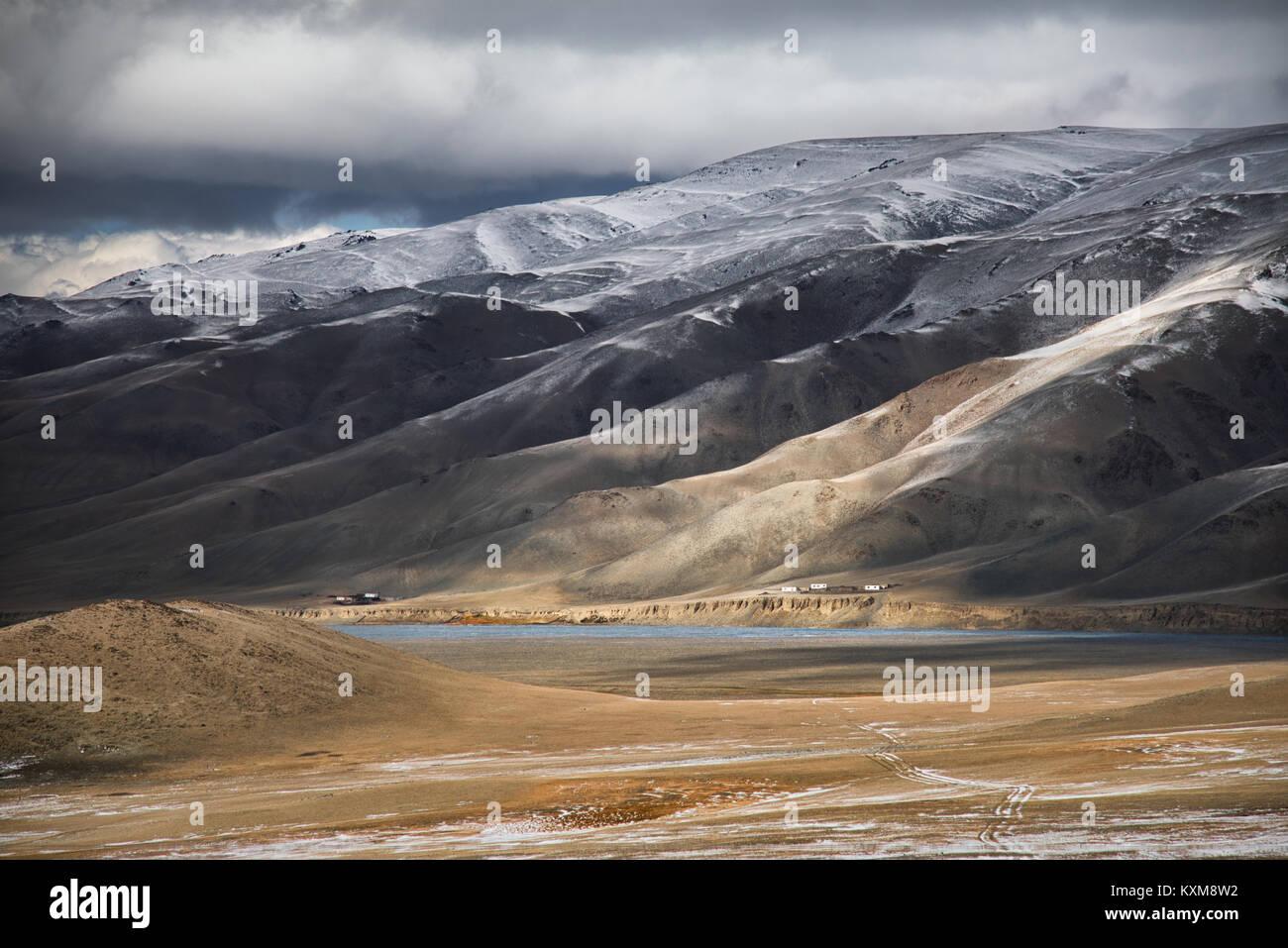Mongolian landscape snowy mountains snow winter cloudy Mongolia - Stock Image