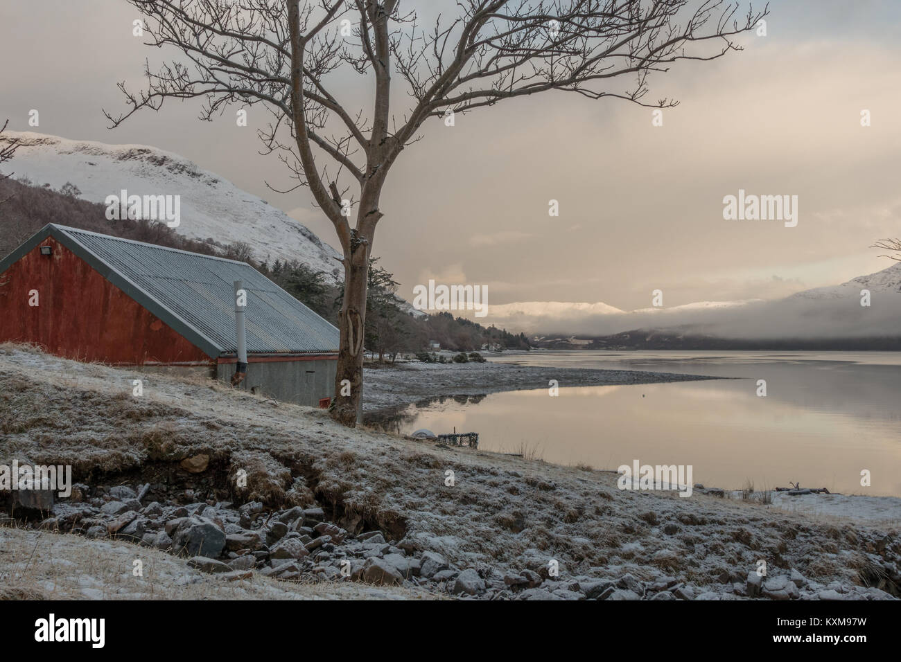 View across Loch Broom to the snowy mountains from the snow-covered shore and boathouse at Letters, Ullapool, Scottish - Stock Image