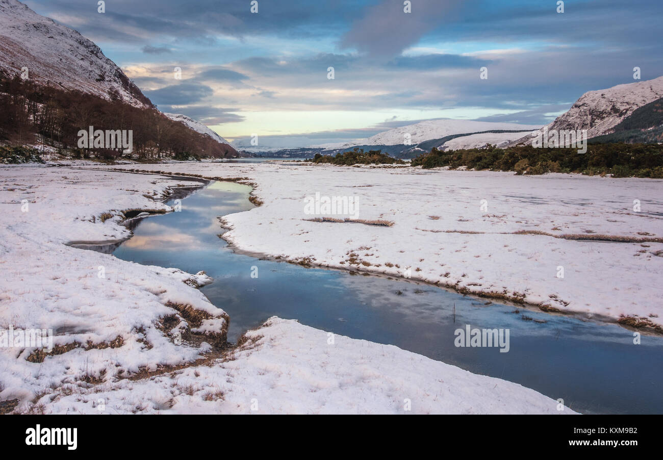 UK winter landscape: Stunning view down the stream at the mouth of Loch Broom with snowy mountains and snow-covered - Stock Image