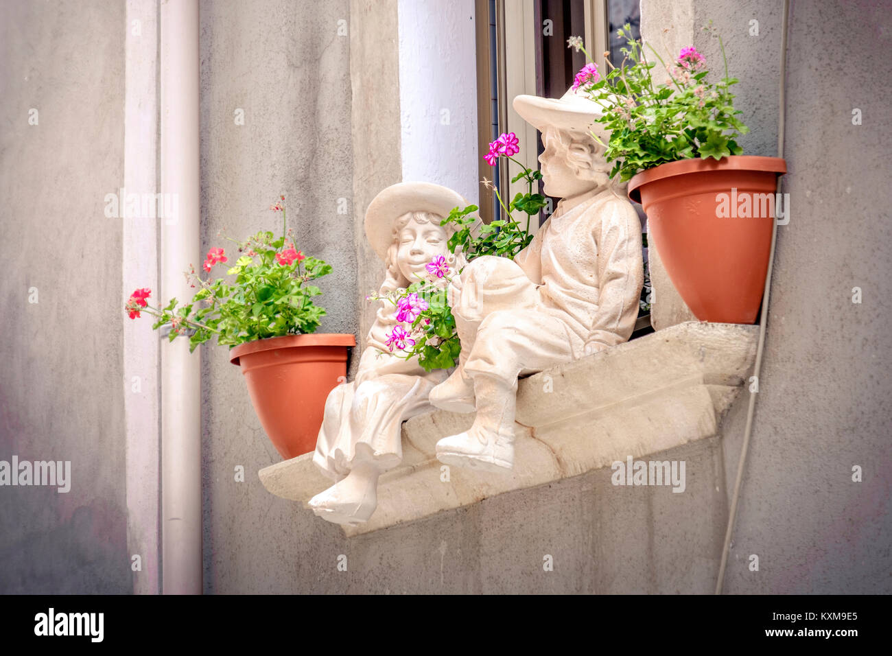 windowsill statues children background flowerpots balcony window sill - Stock Image
