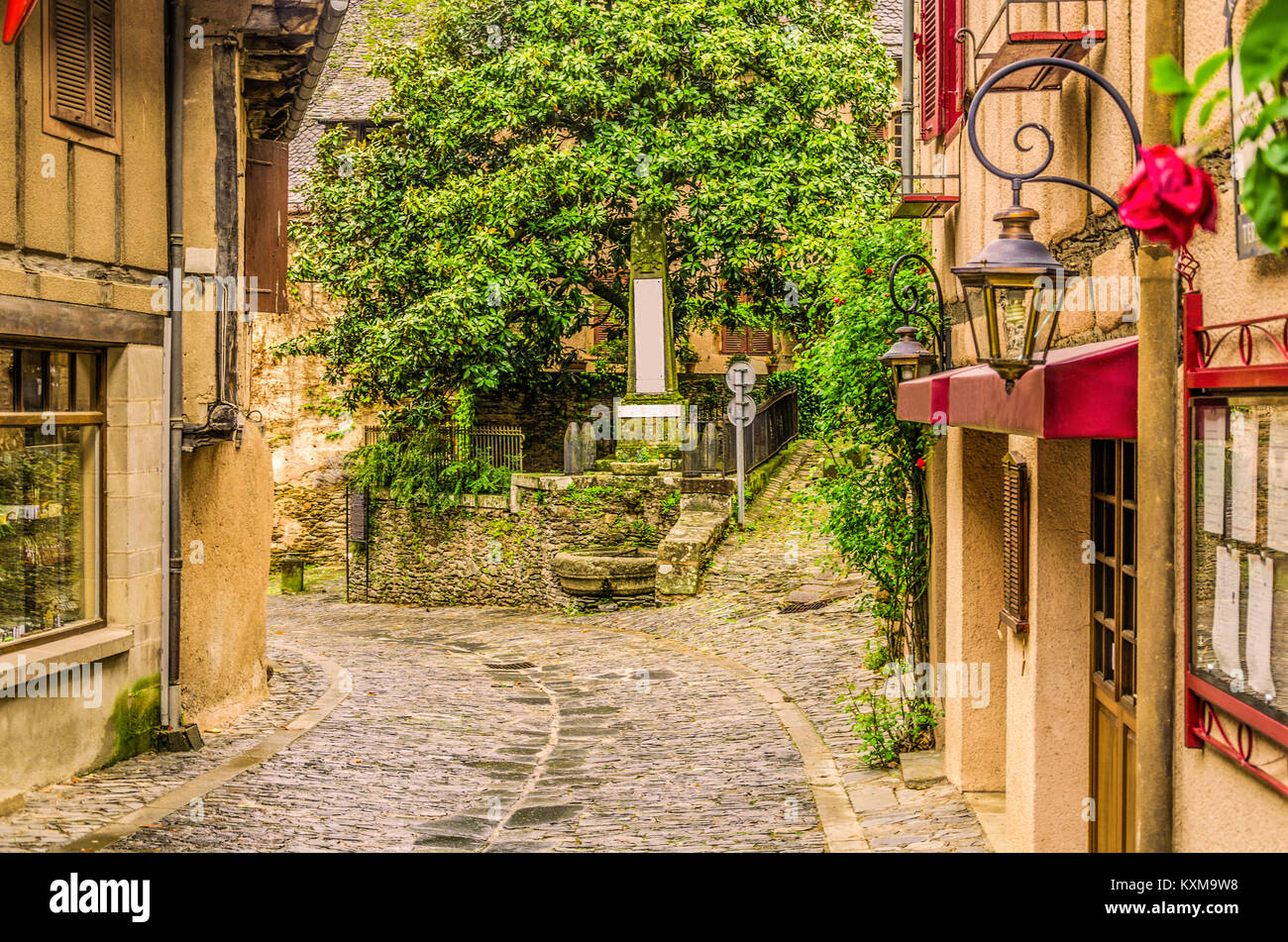 Crossing of narrow streets and monolith to the fallen ones in the war in the old medieval village of Conques on - Stock Image