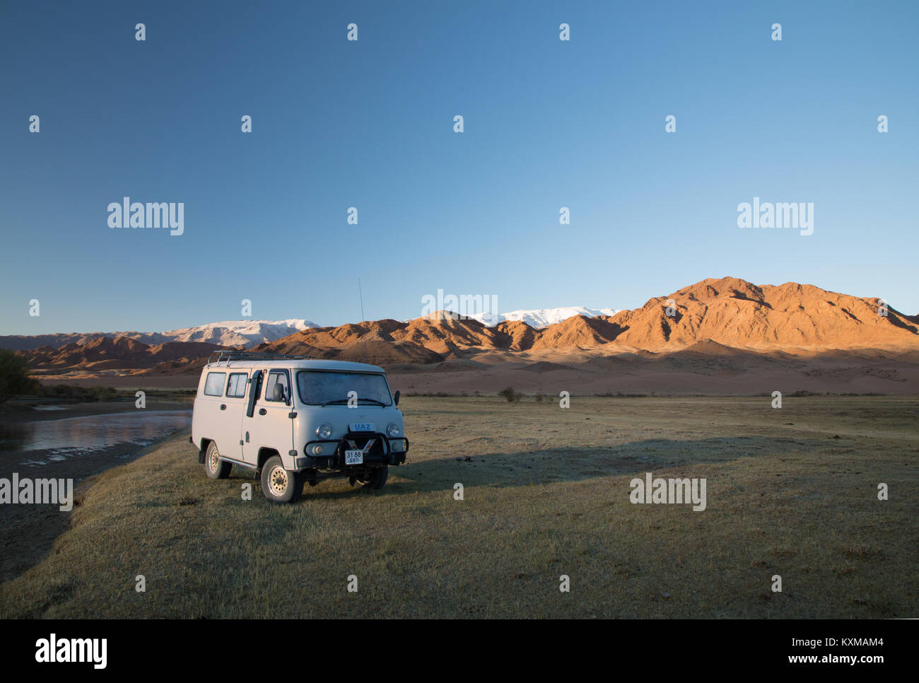 Russian van UAZ452 camper van offroad 4x4 sunrise light cold morning Mongolia landscape mountains - Stock Image