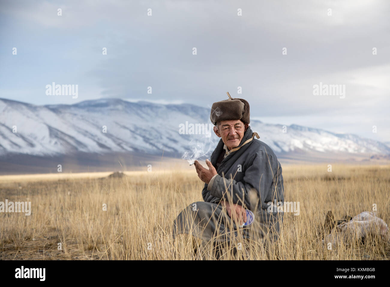Mongolian country side rural old man smoking cigarette fur hat Mongolia grandfather seating resting - Stock Image