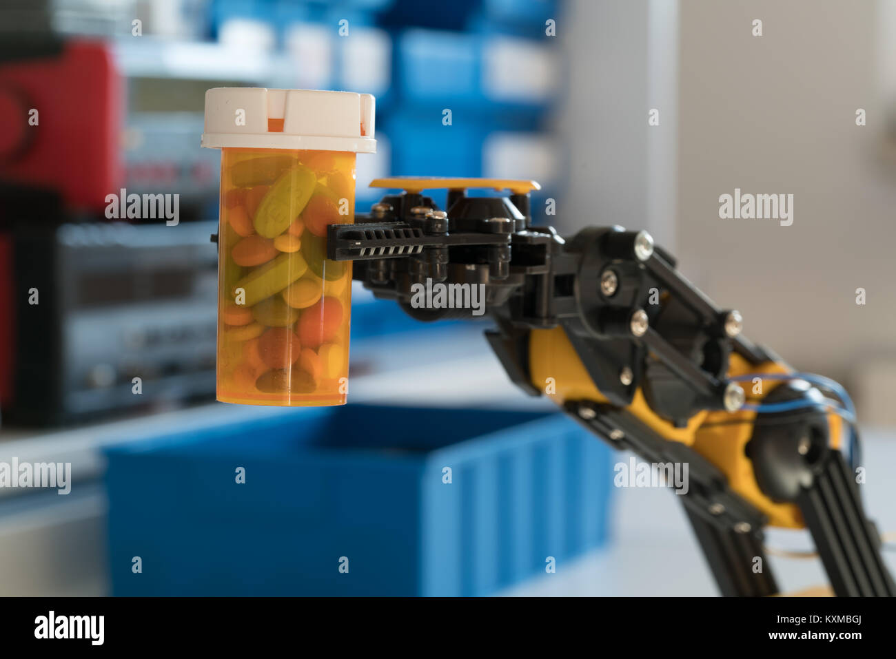 robot arm holds a bottle of pills - Stock Image
