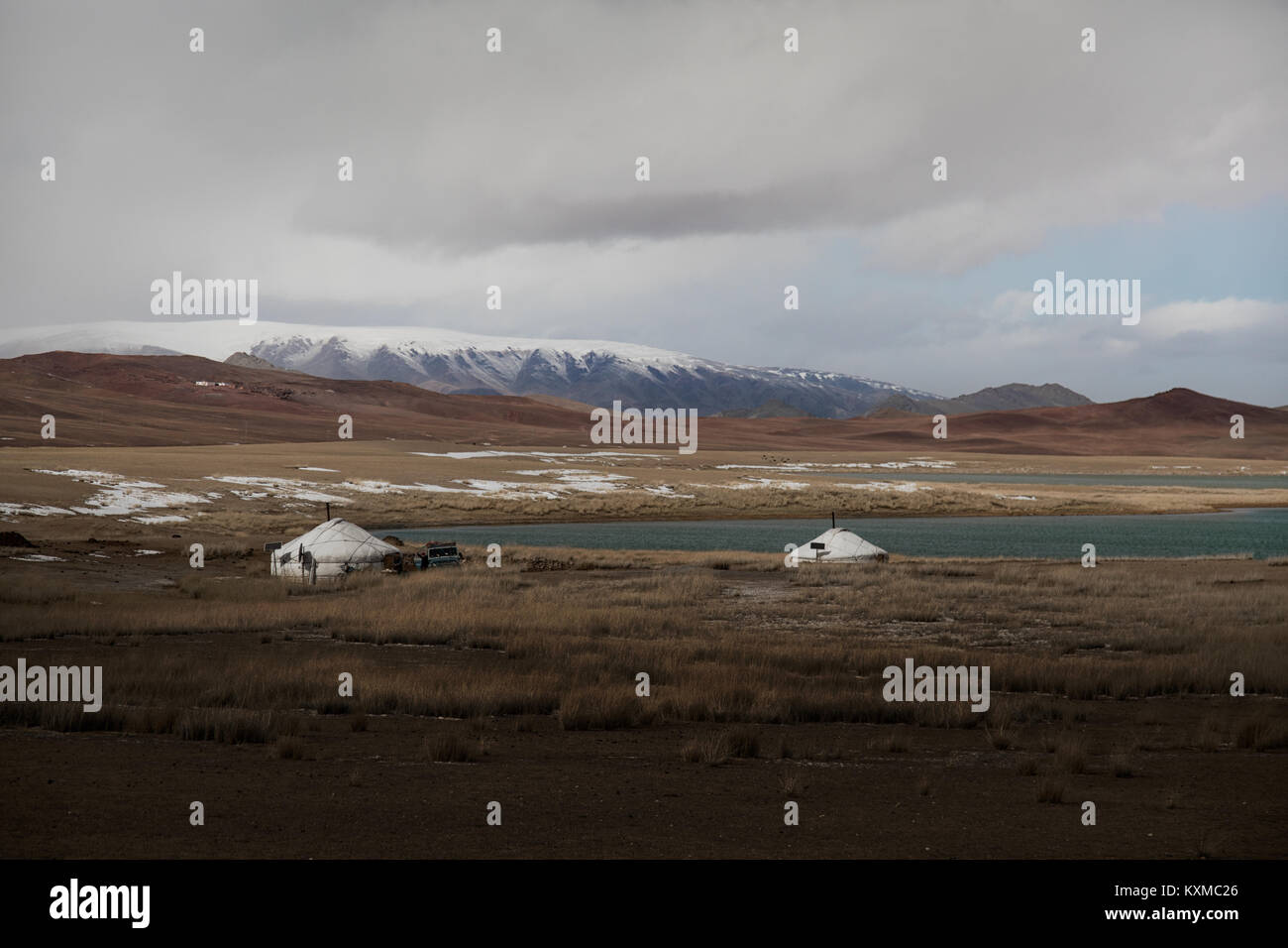 Mongolia gers winter lake snowy mountains cloudy grasslands steppes Mongolian - Stock Image