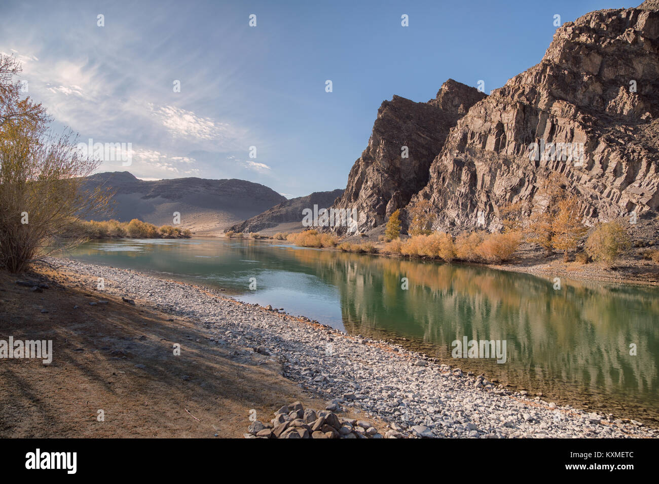 Green river bank yellow leafs fall golden hour calm stream river reflections cliffs Mongolia - Stock Image