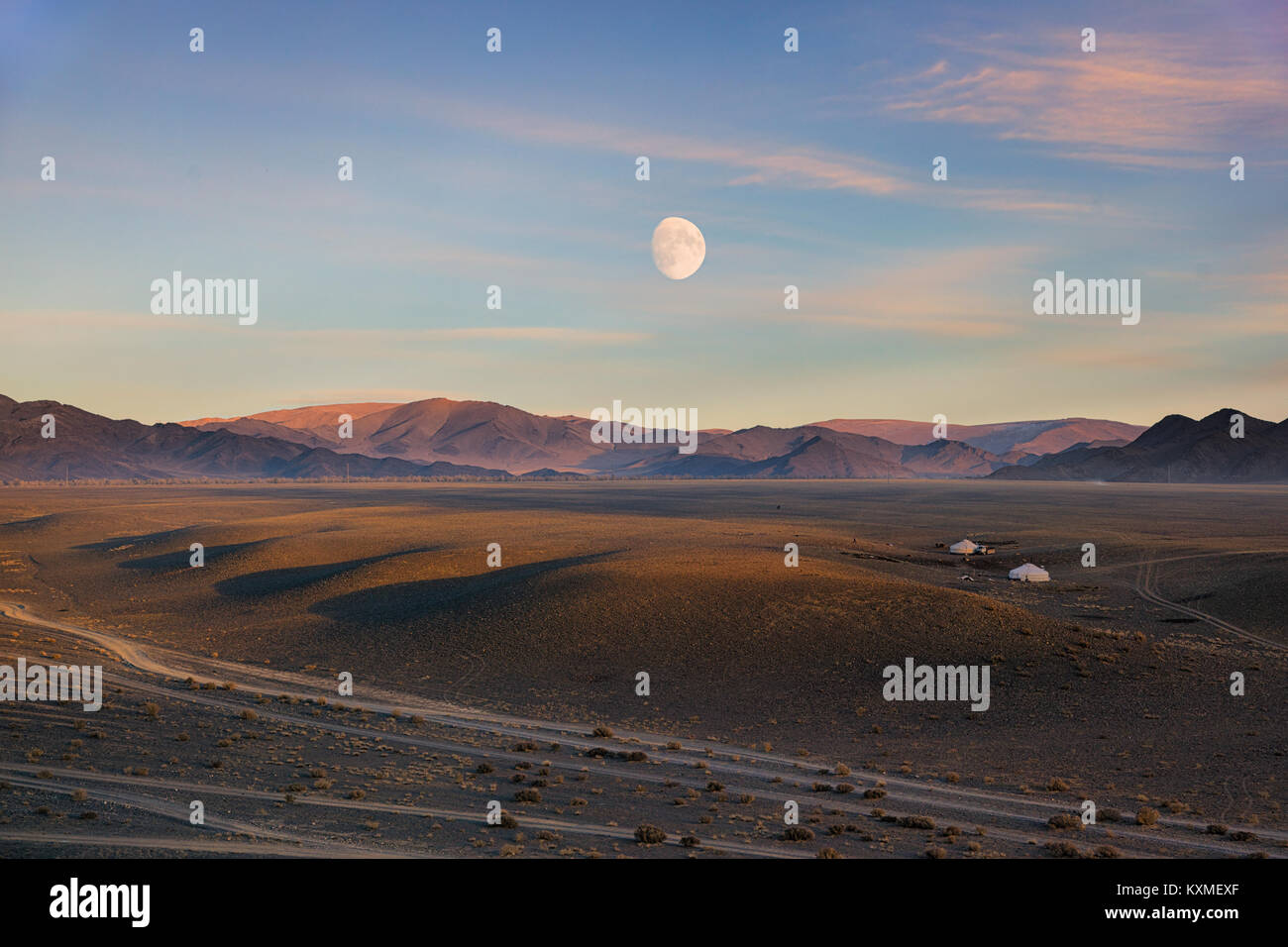 Mongolian sunset moon gers landscape steppes grasslands dirt roads golden hour - Stock Image