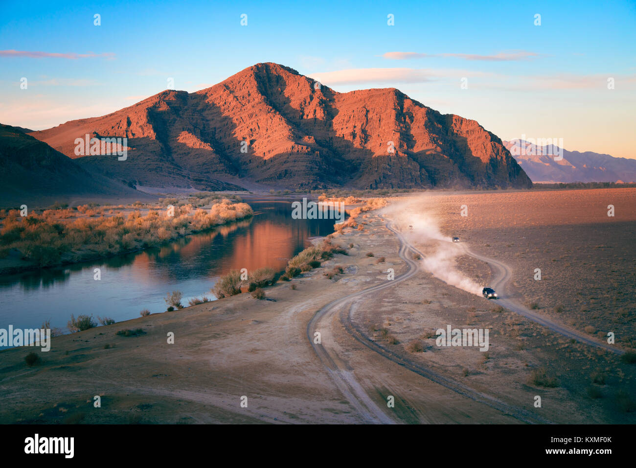 Dirt road cars racing dust cloud sunset landscape Mongolia red mountain river reflection - Stock Image