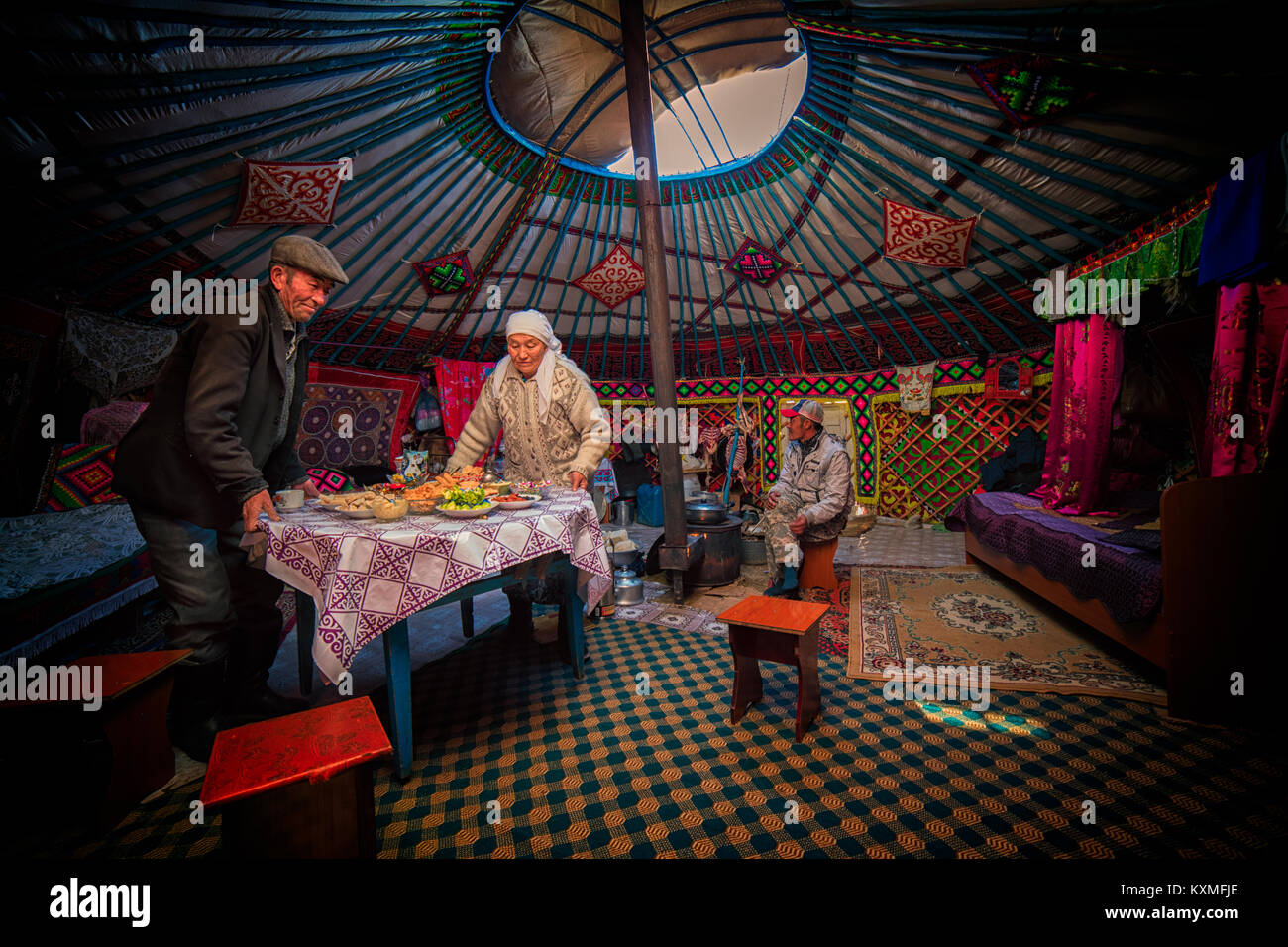 Rural old couple Mongolian Kazakh eagle hunter family serving dinner table inside ger - Stock Image
